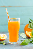 Orange juice in glass and fresh fruits with leaves on wooden background Royalty Free Stock Photo