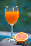 Orange juice in glass with fresh orange Stock Images
