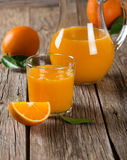 Orange juice glass and fresh oranges with leaves Stock Images