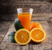 Orange juice glass and fresh oranges on wood Royalty Free Stock Photography