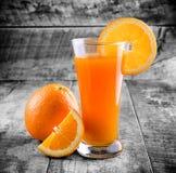 Orange juice glass and fresh oranges Royalty Free Stock Images