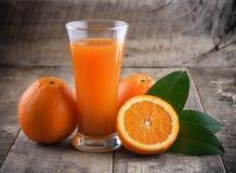 Orange juice glass and fresh oranges on wood Stock Photography