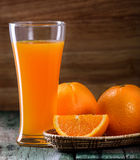 Orange juice glass and fresh oranges on wood Stock Images