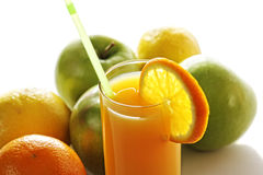 Orange juice in glass in front of fruits Royalty Free Stock Photography