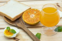 Orange juice in glass with heathy foods on wood table Royalty Free Stock Photos