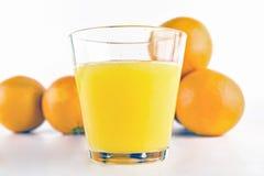 Orange juice. Glass of orange juice, and whole oranges on white background Royalty Free Stock Image