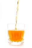 Orange juice into the glass isolated Royalty Free Stock Photos