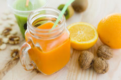 Orange juice in glass, nuts and fresh fruits on wooden backgroun Stock Photos