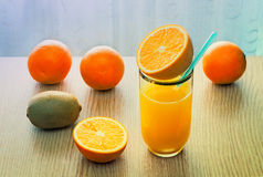 Orange juice in a glass and oranges on the table. Stock Images