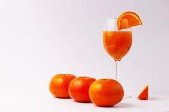 Orange juice glass with oranges Stock Images