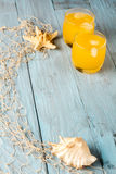 Orange juice in glass and seashells Stock Images