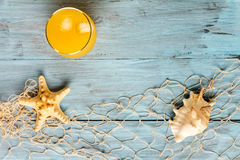 Orange juice in glass and seashells Royalty Free Stock Images