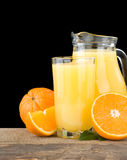 Orange juice in glass and slices on black. Background Stock Image