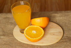 Orange juice and a glass top view. Half a glass of orange juice on the cutting board  background Stock Photo