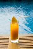 Orange juice in a glass on the wooden table by the pool. Juice Royalty Free Stock Images