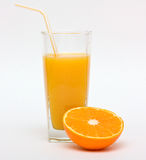 Orange juice and a half of the fruit. Glass of orange juice with straw and a half of the fruit on white background Royalty Free Stock Photos