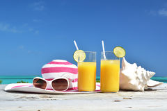 Orange juice, hat, sunglasses and conch on the tropical beach Royalty Free Stock Photography