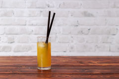 Orange juice with ice in glass and straw in cafe. Orange juice with ice in glass with a straw on dark wooden table in cafe royalty free stock image
