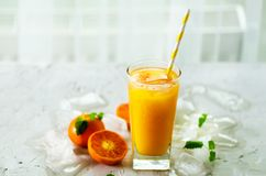 Orange juice with ice and tangerines on white background. Free space for your text. Copyspace. Cold beverage for hot royalty free stock photo