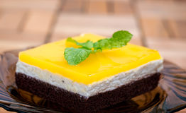 Orange Juice Jello Cake. Lateral view of chocolate sponge, cheese cream filling and orange juice jello topping cake decorated with mint leaves Royalty Free Stock Images