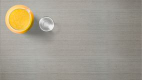 Orange juice jug with glass on grey background stock photos