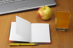 Orange juice,laptop,apple notepad and pen Stock Photography