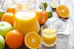 Orange juice with lime grapefruit and squeezer Stock Photos