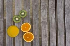 Orange juice, oranges and kiwis on a table. Orange juice, oranges and kiwis on a wooden table royalty free stock images