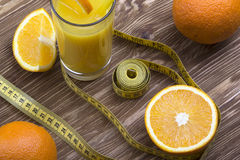 Orange juice, oranges and measuring tape Royalty Free Stock Photo