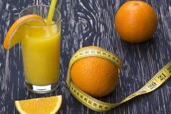 Orange juice, oranges and measuring tape Royalty Free Stock Photography