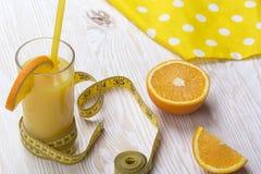 Orange juice, oranges and measuring tape Stock Photos