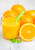 Orange juice and oranges with mint. On white table Royalty Free Stock Photos