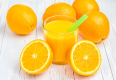 Orange juice and oranges. On wooden table Stock Photos
