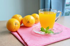 Orange juice and oranges on wooden table. Royalty Free Stock Photos