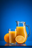 Orange juice over blue Stock Images