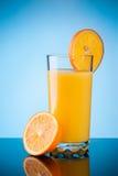 Orange juice over blue Royalty Free Stock Image