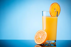Orange juice over blue Stock Photos