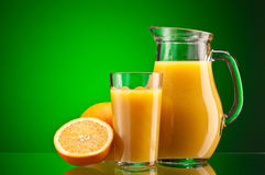 Orange juice over green Stock Photo