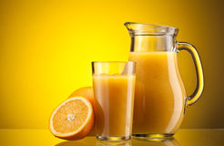 Orange juice over yellow Royalty Free Stock Images