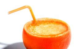 Orange juice in the peel. Juice to orange peel with a straw.  with shadow Royalty Free Stock Photo