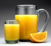Orange juice with pitcher. Orange juice on grey with pitcher Stock Photo