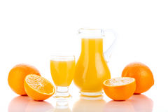 Orange juice in pitcher and oranges Stock Photography