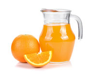 Orange juice in pitcher and oranges. Royalty Free Stock Images