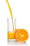Orange juice poring into glass Stock Images