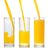 Orange juice poring into glass Stock Photos