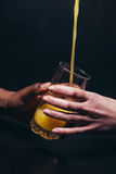 Orange juice pour in glass, black and white hand Royalty Free Stock Photography