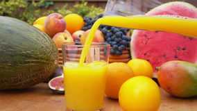 Orange juice is poured into a glass. On a background of a still-life of fresh fruit on a wooden table stock video footage