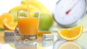 Orange juice poured in glass, fruit meter scales diet food stock video