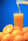 Orange Juice Pouring. On blue background Stock Photos