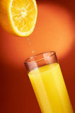 Orange juice pouring Stock Image